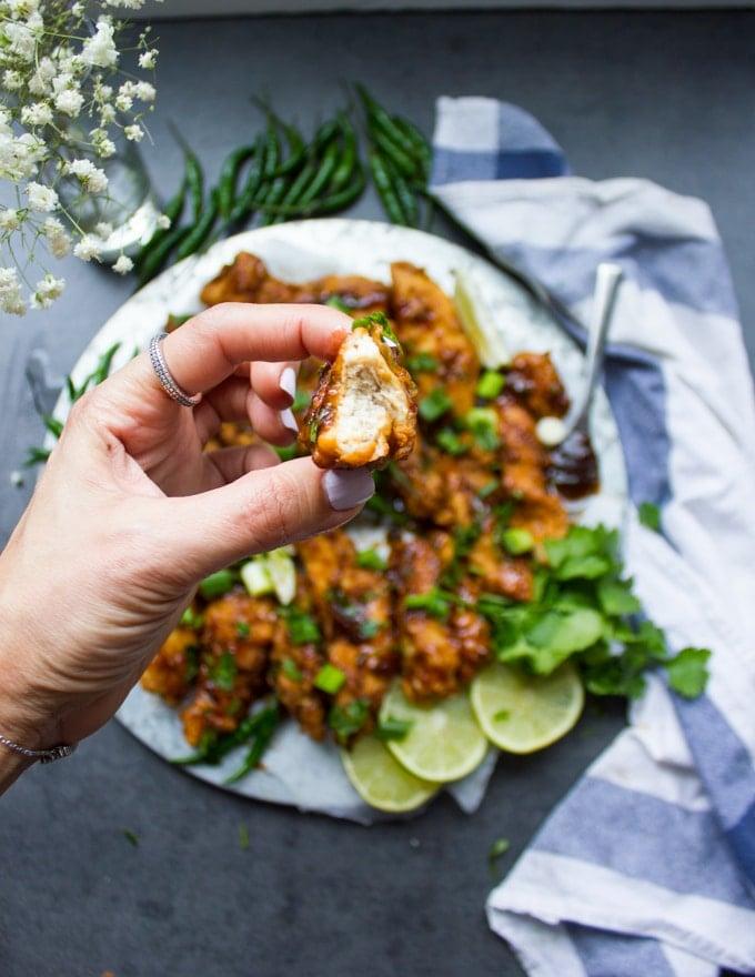 A hand holding a piece of fried Korean Chicken bitten to show the inside