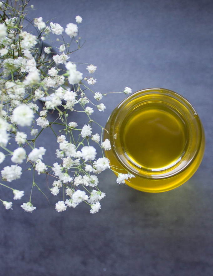 A top view bottle of soybean oil and white flowers