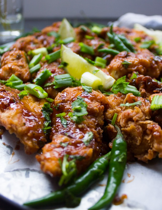 Close up of fried chicken strips with green chillies next to it and drizzled with the Korean Fried Chicken Sauce