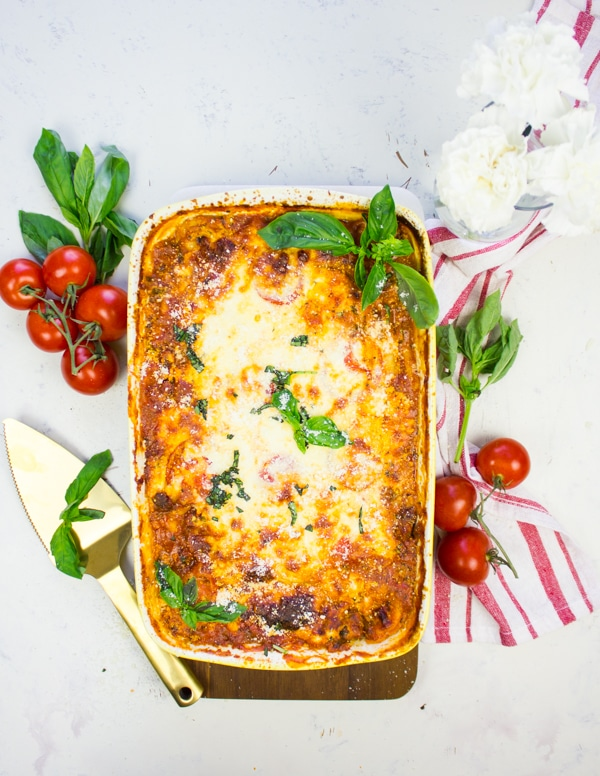A big dish of homemade lasagna surrounded by a red tea towel, fresh basil leaves and a baby vine ripe tomatoes
