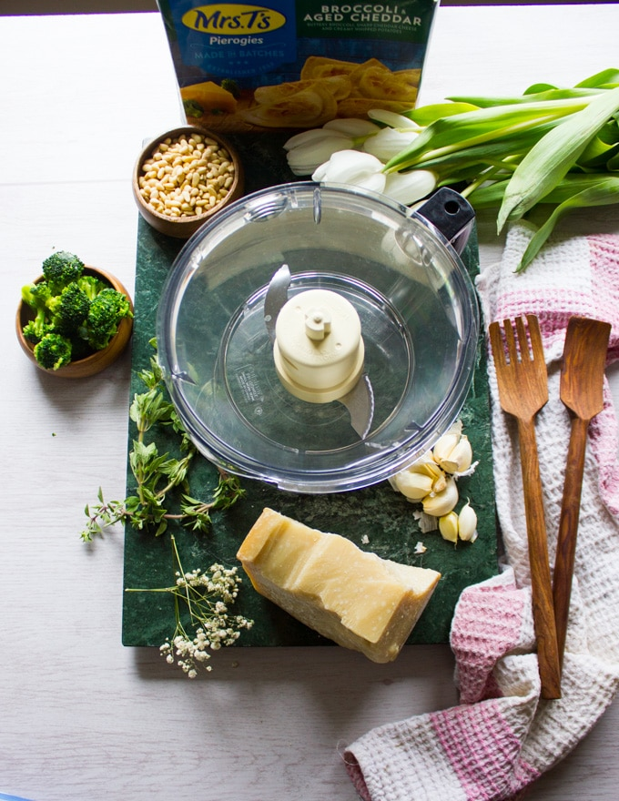 Ingredients for the broccoli pesto and a food processor to make it. Broccoli, parmesan cheese, garlic, pine nuts, herbs and olive oil