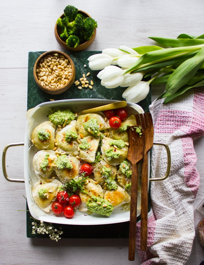 One pan baked pierogies with the broccoli pesto and pine nuts, surrounded by white tulips and a kitchen towel