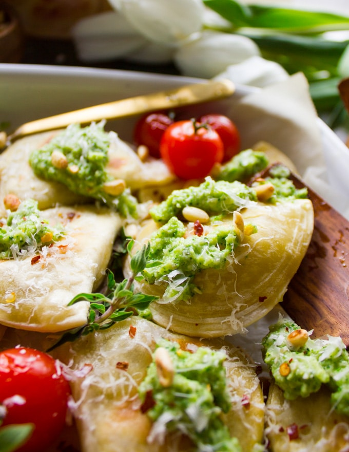 Close up of one baked pierogy with a dollop of broccoli pesto
