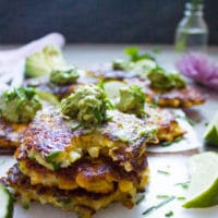 a stack of corn fritters with the last one bitten up to show the texture and a dollop of guacamole