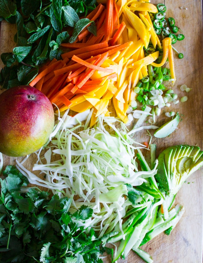 a wooden board with all the salad ingredients chopped: cabbage, mango , carrots, onions, mint leaves, cilantro leabes