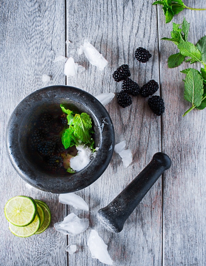 A mortar and pestle with blackberries, lime, sugar and mint surrounded by more mint, lime slices and ice