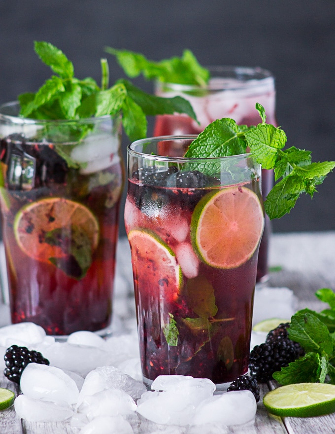 Close up of three cups of blackberry mojitos surrounded by ice