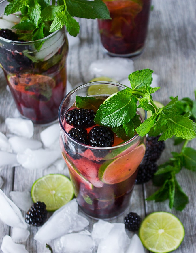 Three different cups of blackberry mojitos with different garnishes, such as blackberries, mint and lime slices