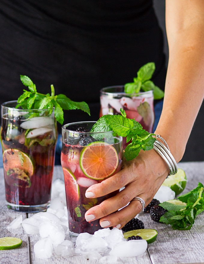 The blackberry mojito is ready to go and a hand is about to pick it up now