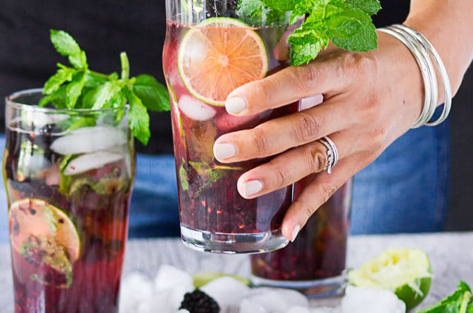 A hand holding a cup of blackberry mojitos