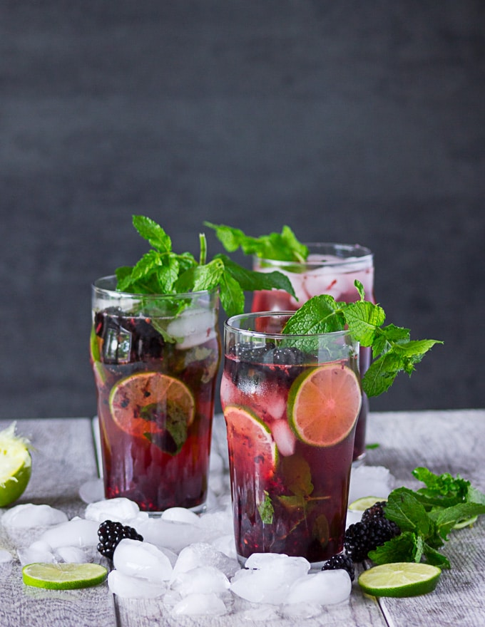 Three cups of prepared mojitos surrounded by ice and garnished with lime, mint and more blackberries