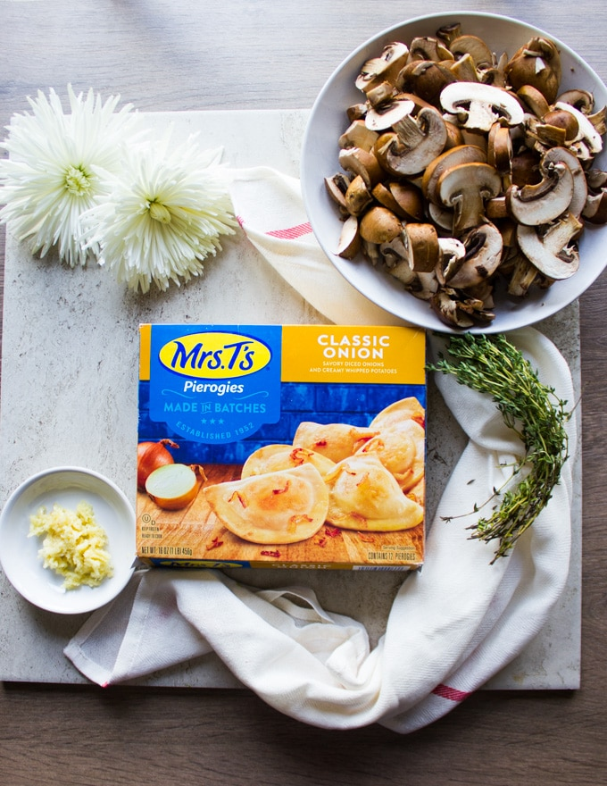 a box of Mrs.T's Pierogies - classic onion flavor surrounded by white flowers, a tea towel, a bowl of mushrooms and fresh thyme leaves