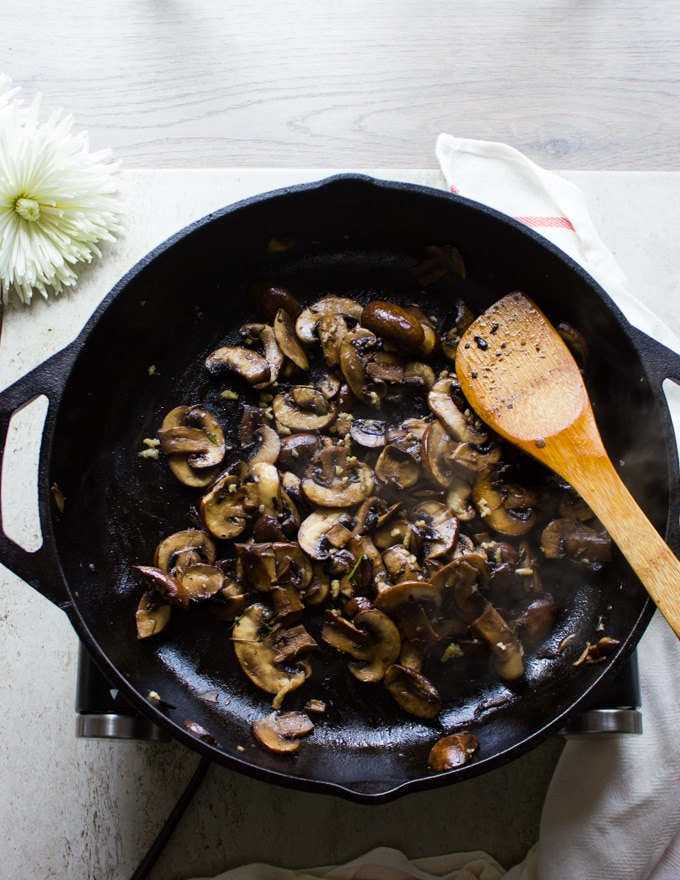 A large pan with the mushrooms and garlic sauteed together with a wooden spoon