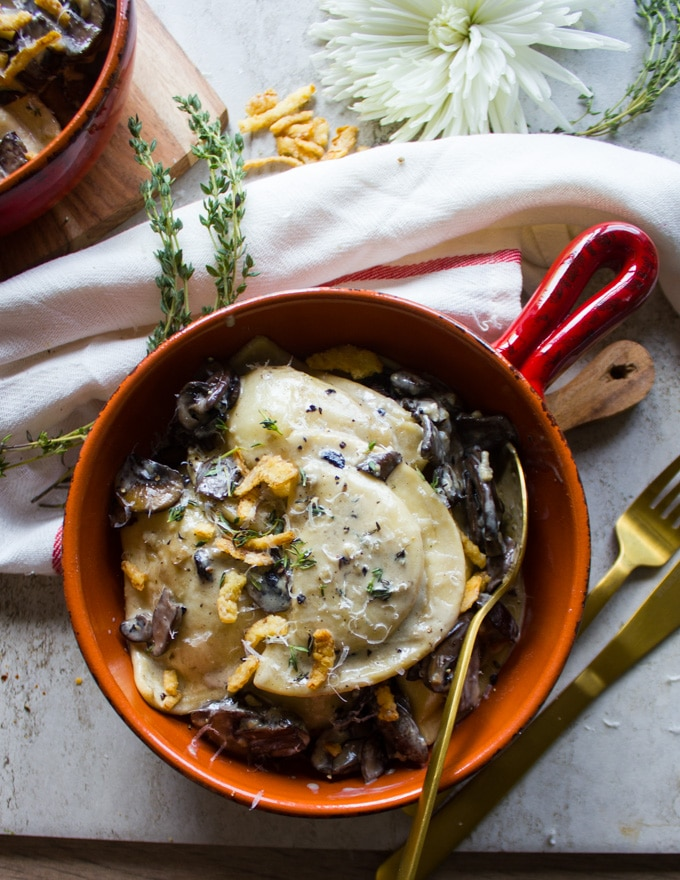 One bowl of Alfredo Recipe with pierogies, mushrooms, crispy onions and a fork