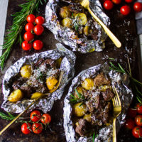 three packets of foil on the grill showing the lamb and potatoes with parmesan cheese, rosemary and tomatoes on the sides with three forks.