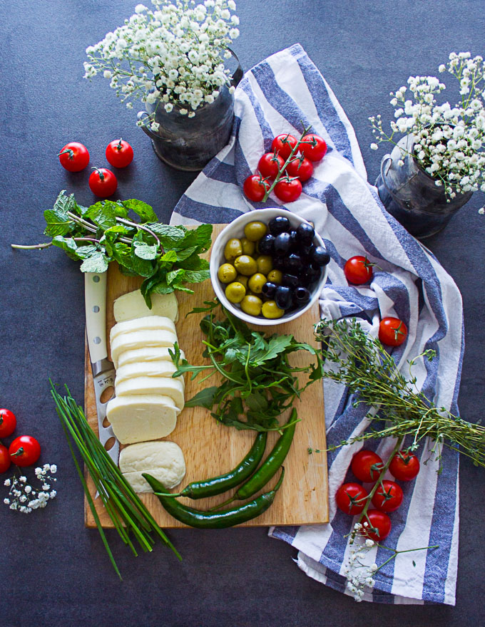 ingredients for the halloumi cheese salad on a cuttng board including olives, tomatoes, fresh mint