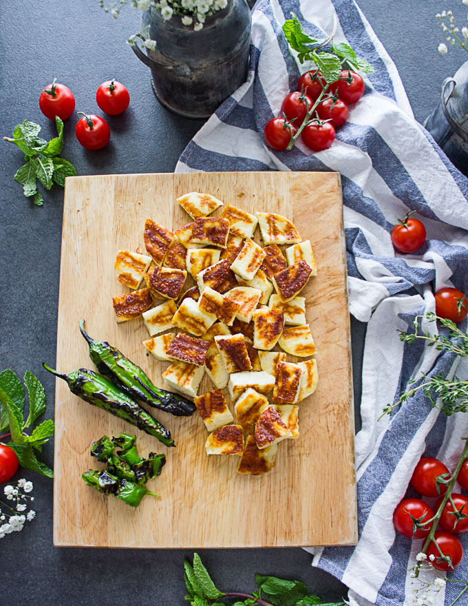 A cutting board with the grilled chopped halloumi cheese and shitsito peppers