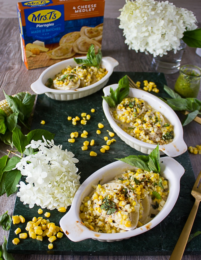 4 ramekins with corn casserole made using pierogies on a marble board surrounded by corn kernels, fresh basil and a box of pierogies