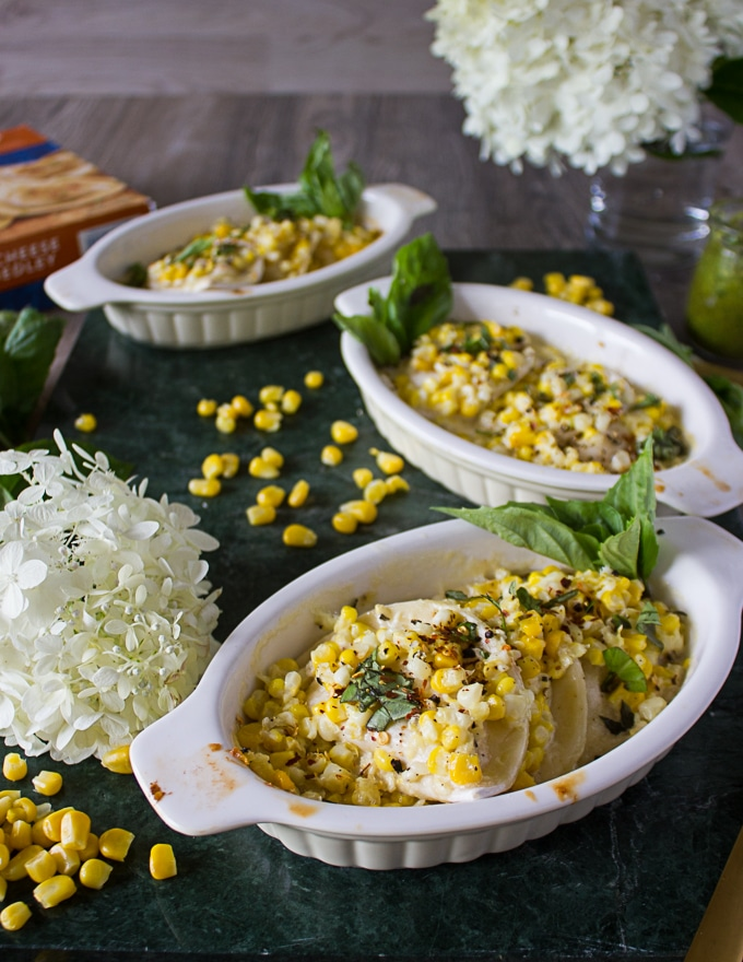 three ramekins of corn casserole surrounded by corn kernels, white flowers on a marble
