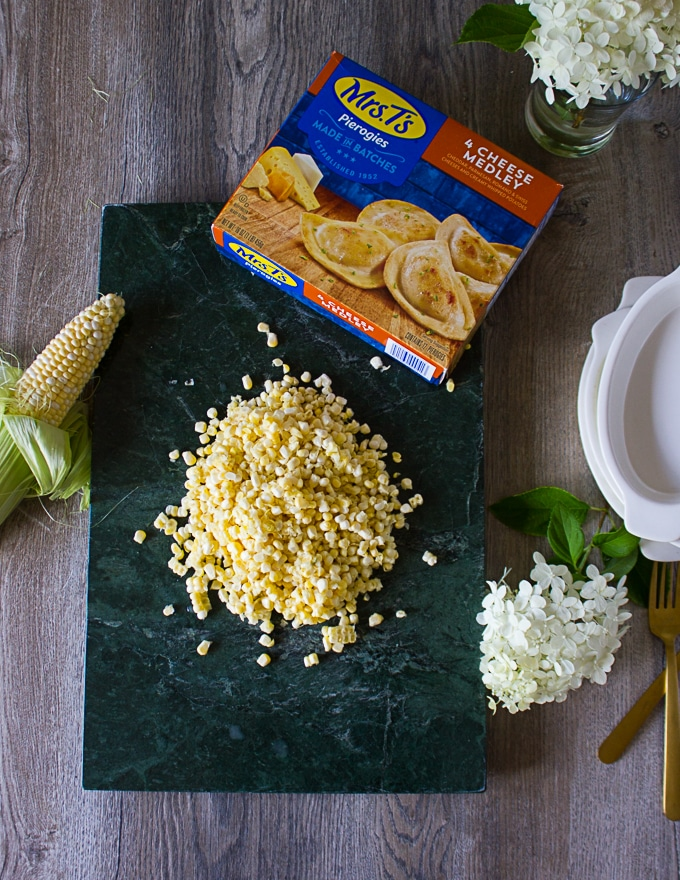 Ingredients for corn casseole over a marble board: the pierogies box, corn kernels, cream, ramekins and garlic