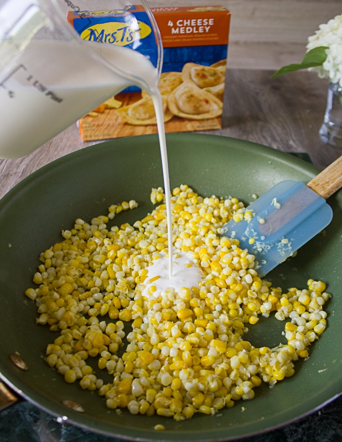 Corn kernels cooking in the garlic butter skillet and cream being added over it