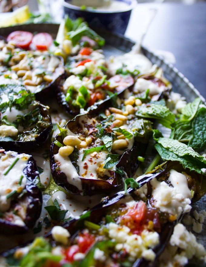 Side view of a fried eggplant half topped with tahini, pine nuts and surrounded by lots of fresh mint