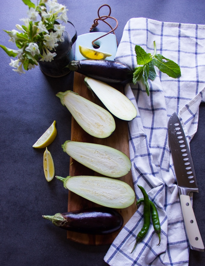 A sharp knife and eggplants sliced in half lengthwise on a cutting board surrounded by a tea towel