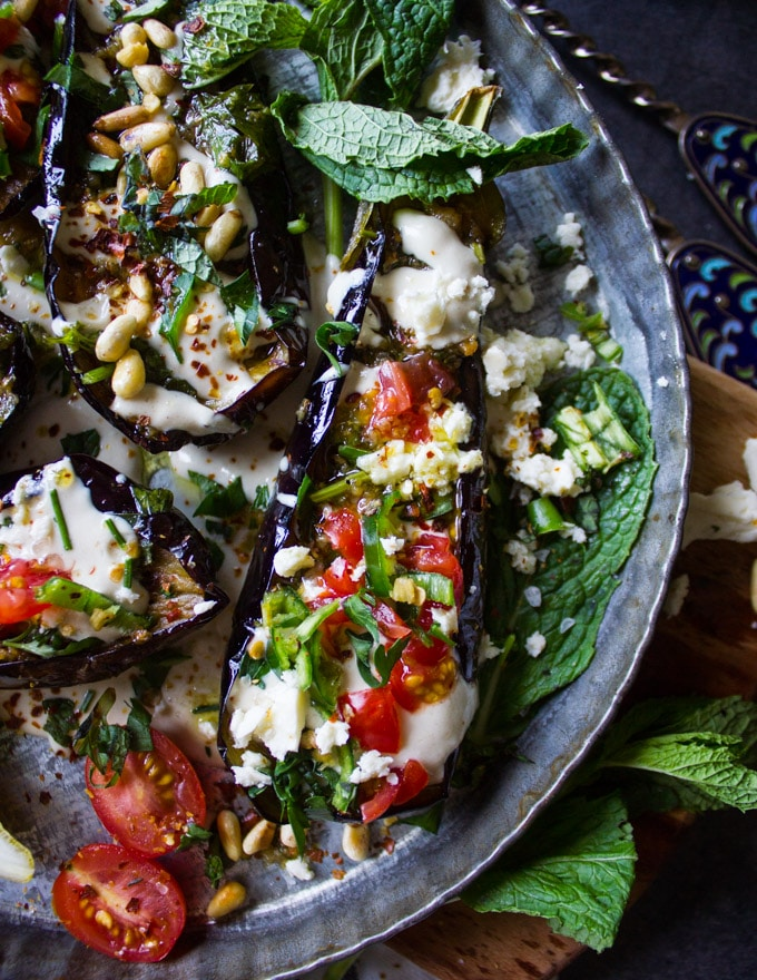 fried Eggplant topped with tahini, tomatoes, feta and green chillies on a bed of tahini sauce