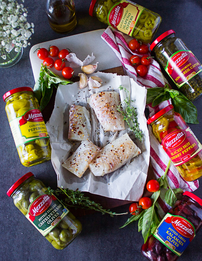 Haddock fillets seasoned on a pan and surrounded by garlic, fresh thyme, baby tomatoes and the jars of olives.