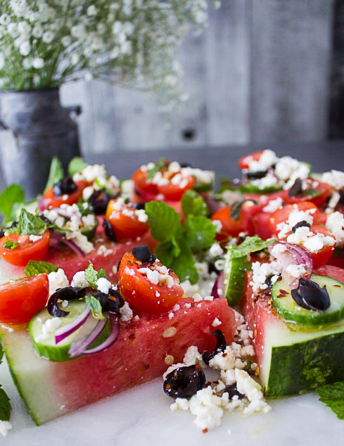 close up of one watermelon salad cut into wedge topped with onions, tomatoes, feta, olives and mint