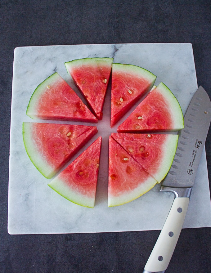 A disc of the watermelon cut up intp eight wedges and ready for the toppings