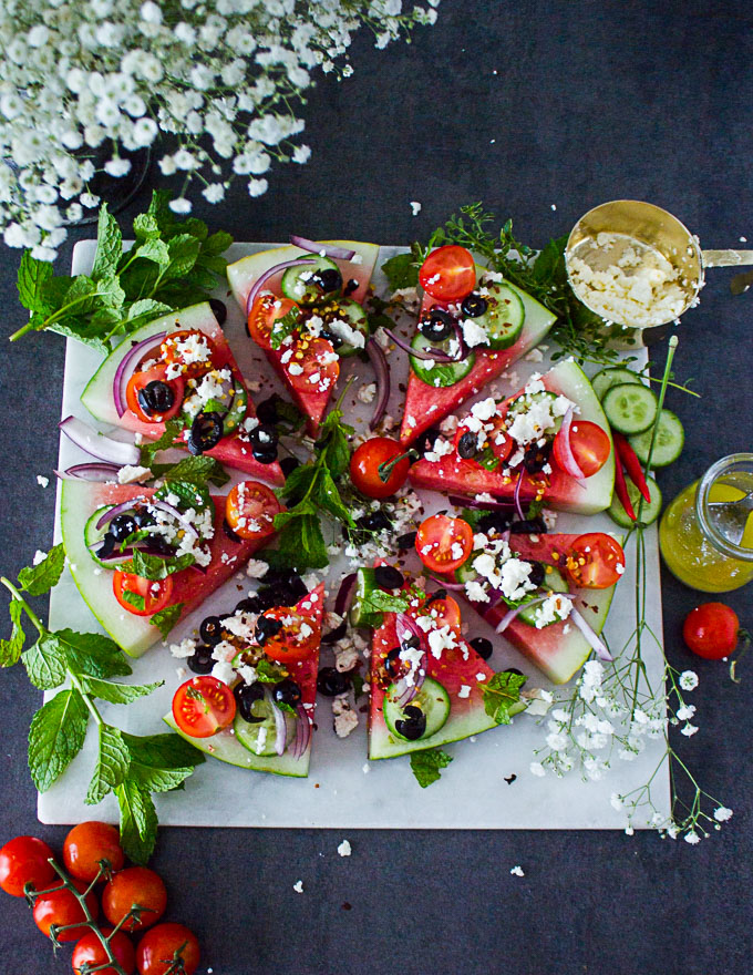 A white marble with watermelon salad loaded with Greek toppings surrounded by mint leaves and white flowers