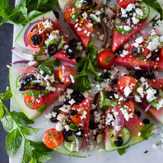 A whole disc of watermelon cut up into wedges and loaded with Greek salad toppings