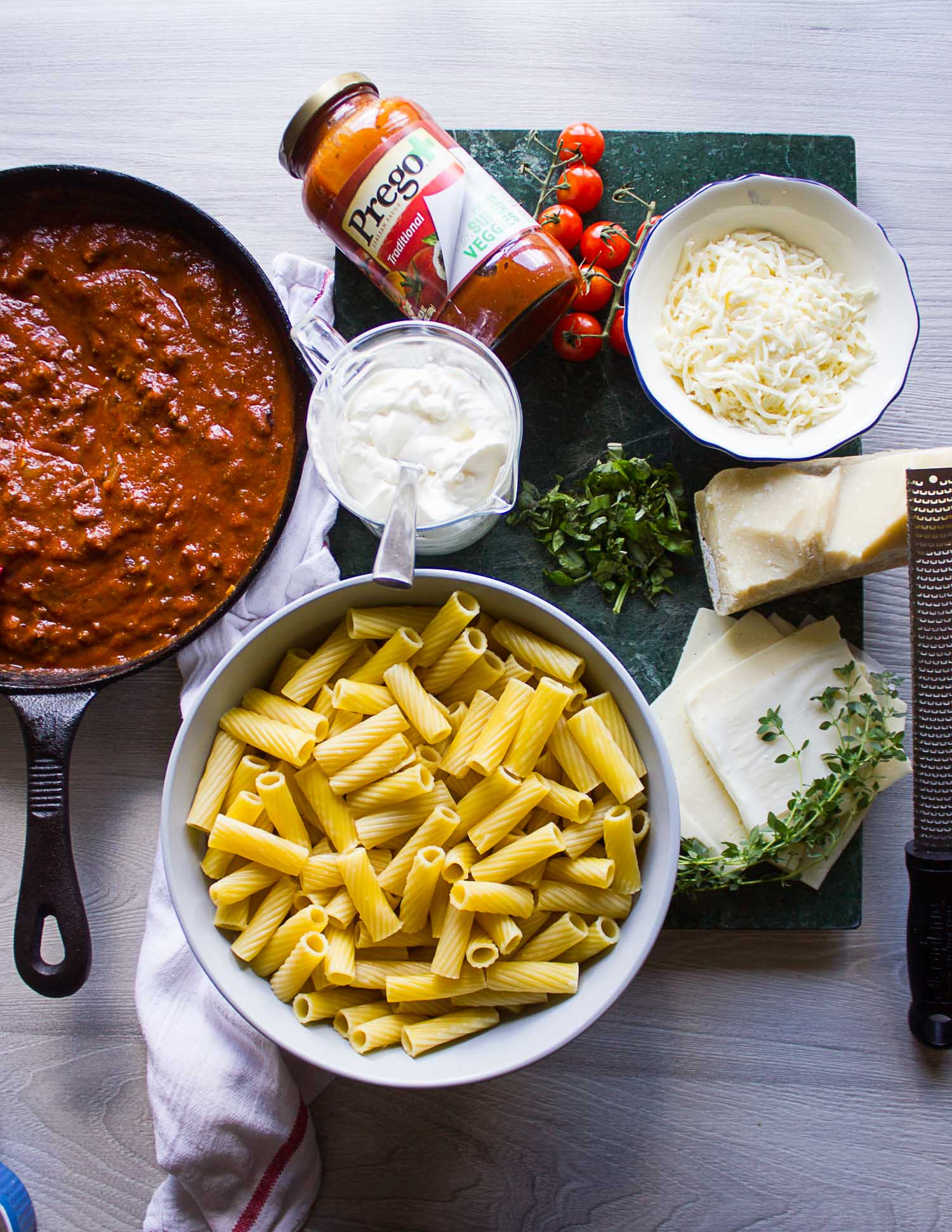 Ingredients for the baked ziti recipe on a board. Includes the cooked ziti pasta, the beef sauce, the cheeses and herbs