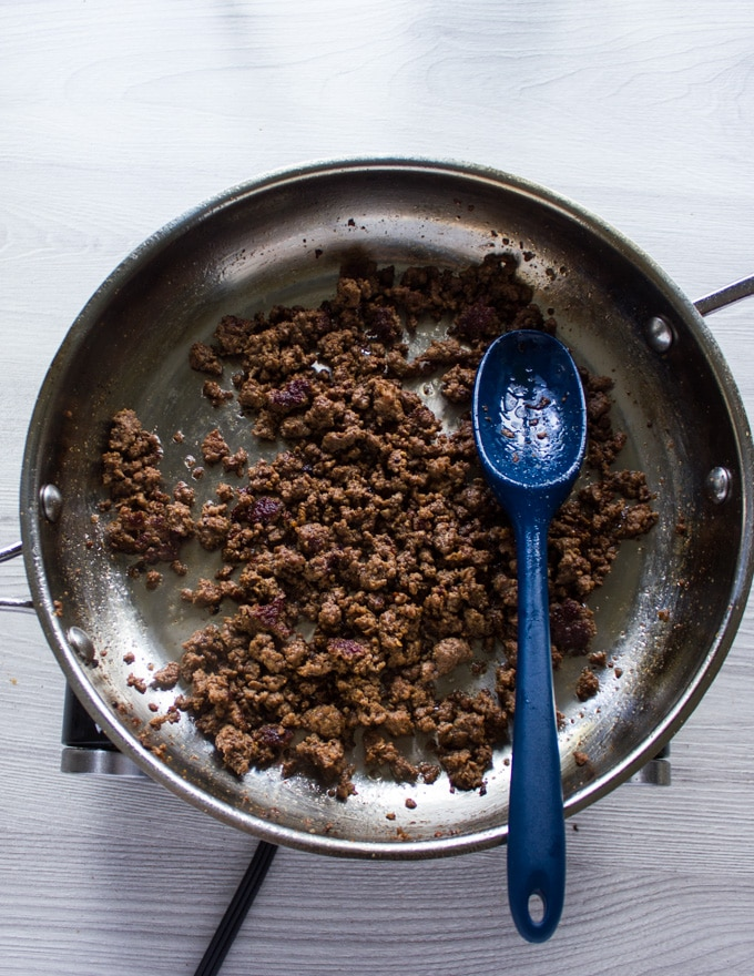 Cooked lamb crumbles in a skillet