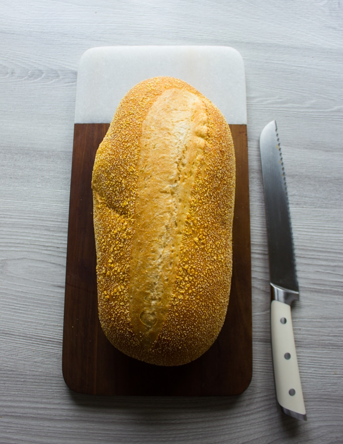 A whole loaf of soft Itlain bread on a cutting board and a serrated knife on the side