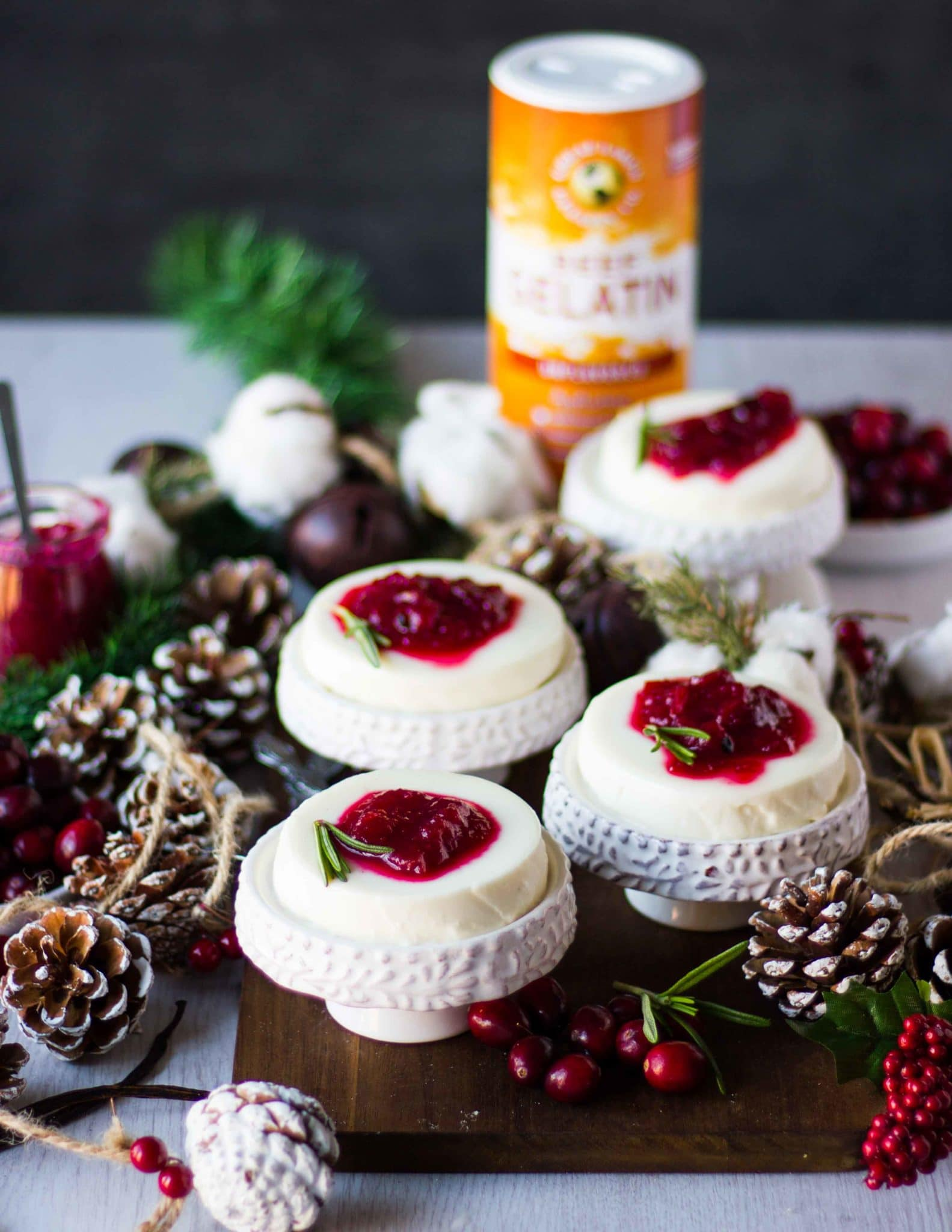 individual servings of four panna cotta recipe on serving plates finished with cranberry sauce and surrounded by fresh cranberries and wooden cones