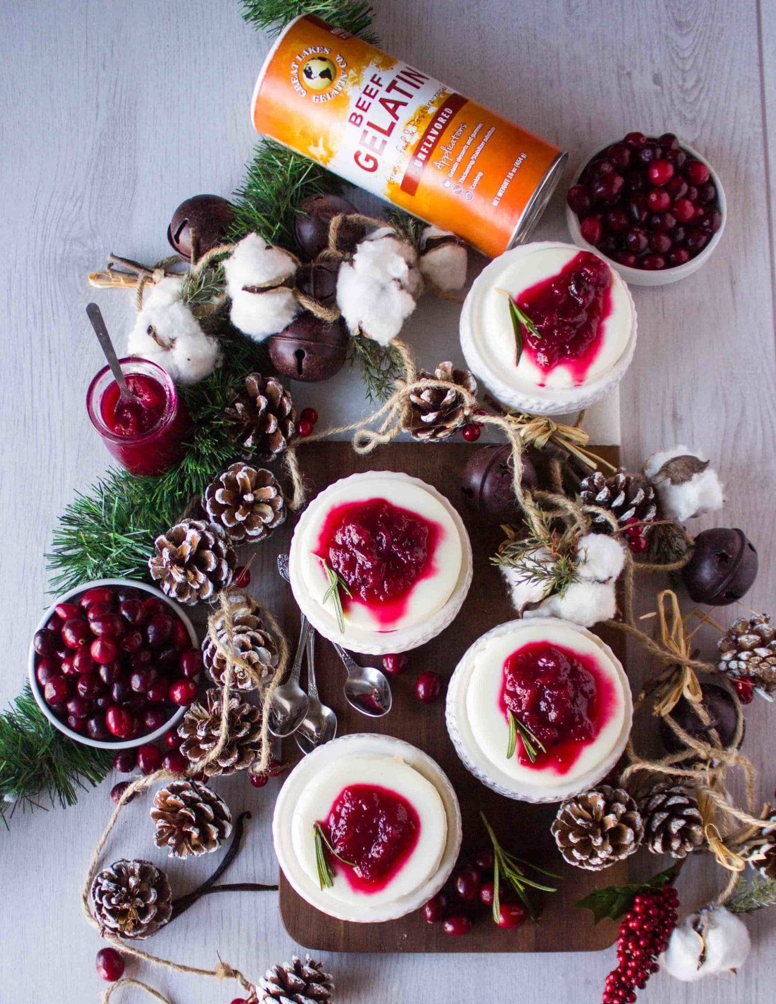 top view of a holiday dessert with tree cones, fresh cranberries and rosemary and 4 panna cotta desserts on serving plates with gelatin