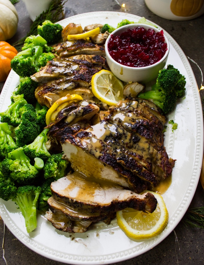 turkey berast recipe, sliced and drizzled with gravy showing one slice in a serving plate with broccoli and lemon slices