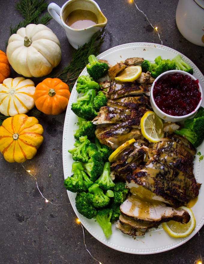 half a plate of turkey breast recipe with pumpkins, gravy and lemon slices