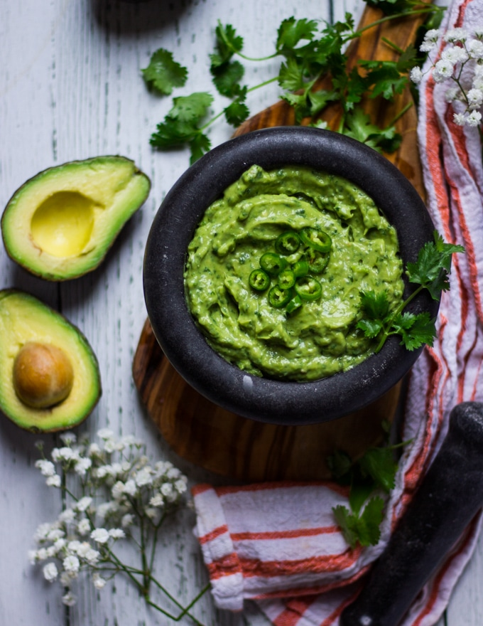 A bowl with guacamole recipe topped with chopped jalapenos and cilantro surrounded by hass avocados and an orange tea towel over a wooden board