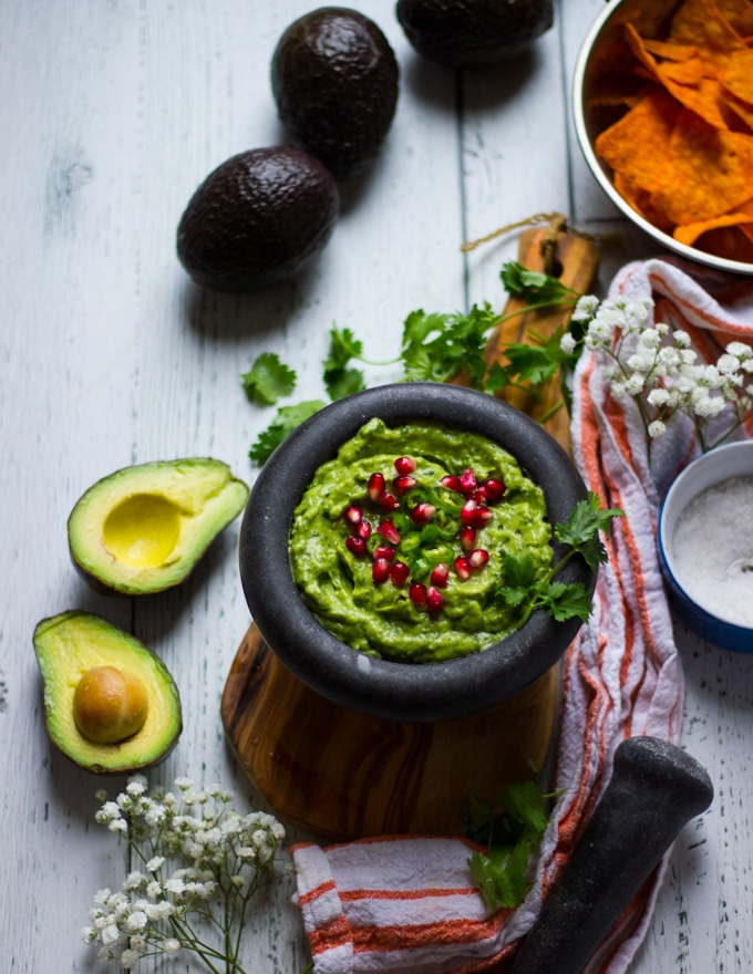 A guacamole recipe simple and topped with some jalapenos and pomegranate arils, not blended in.Some hass avocados around the bowl, a bowl of salt and a bowl of chips