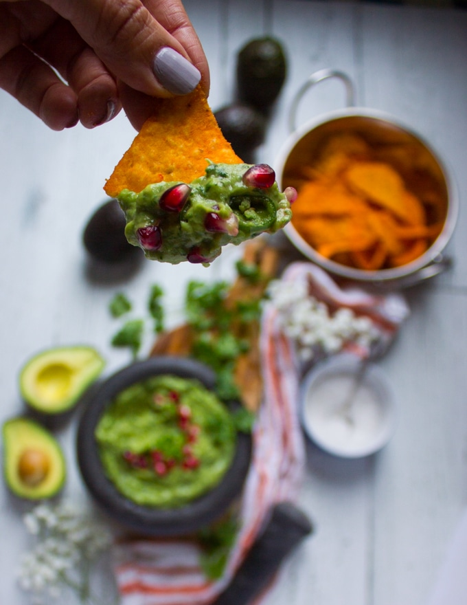 A hand holding a chip dipped in guacamole and close up of the guacamole dip over the chips