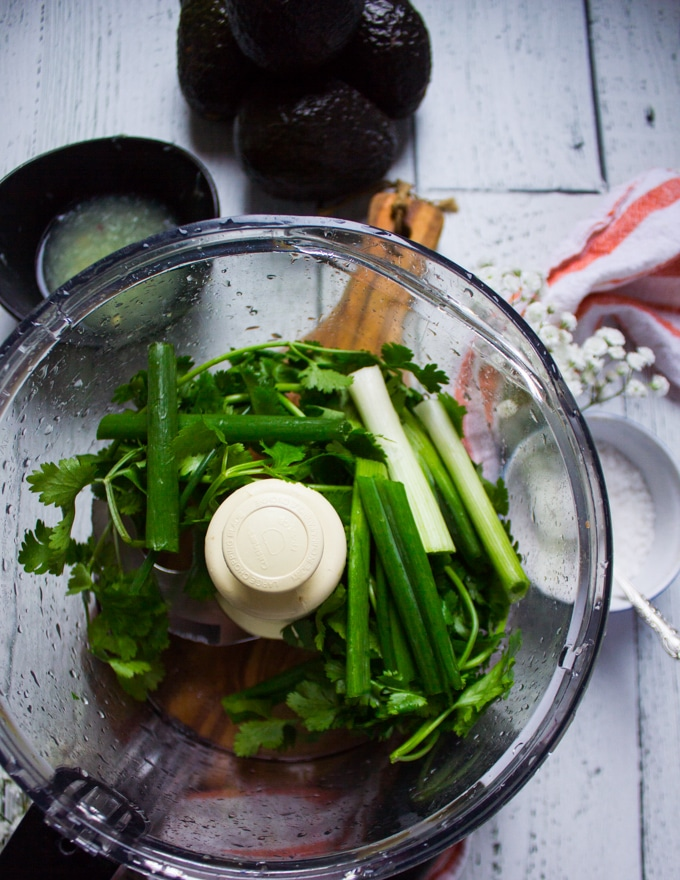 A food processor bowl with cilantro and scallions