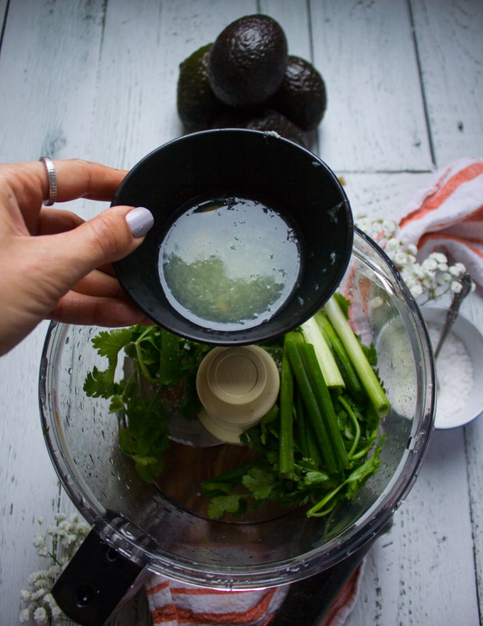 A hand pouring in lime juice from a bowl into the food porcessor with the cilantro and scallions