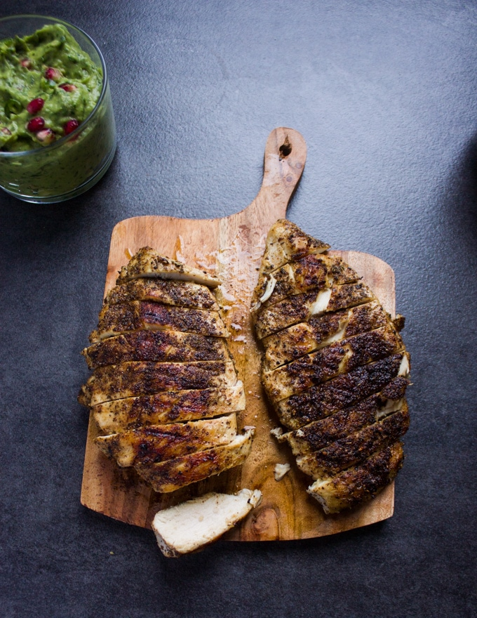 Fully cooked chicken breasts on a wooden board sliced into half an inch slices