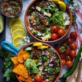 2 ready fajita bowls assembled with the toppings like guacamole, salsa, onion, tomatoes, jalapeno, surrunded by lemon slices, cilantro