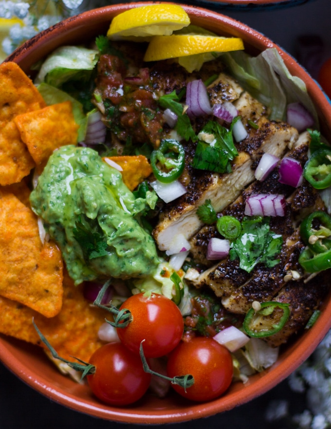 close up of the fajita bowl made using lettuce and chips and layered with chicken, guacamole, salsa and fresh ingredients