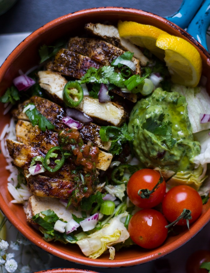 A fajita bowl loaded with chicken fajitas, rice, tomatoes guacamole and salsa