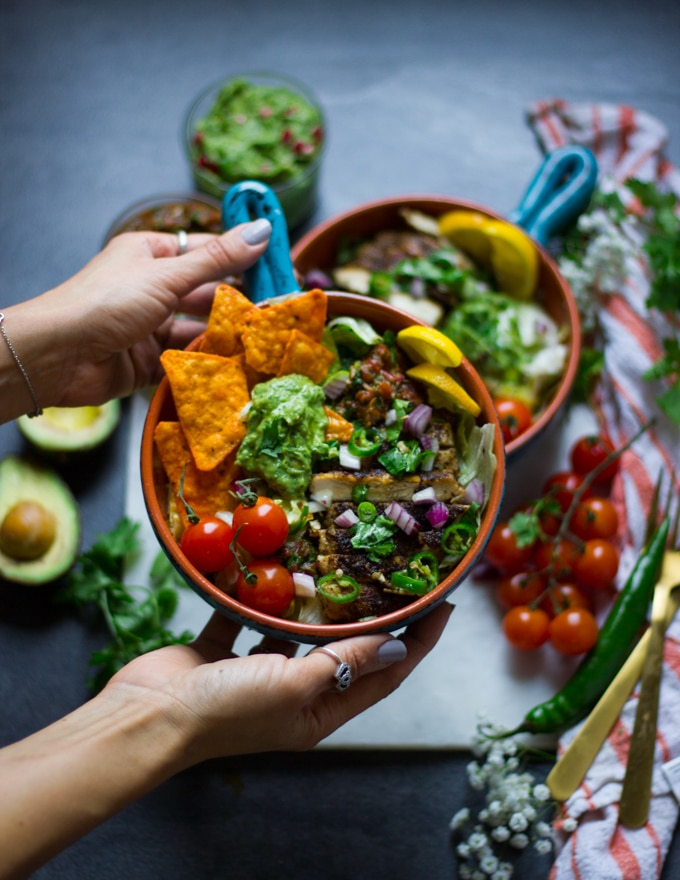 A hand holding a fajita bowl loaded with tomatoes, chips, salsa, guacamole and chicken